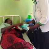 National treasurer -Caroline Adera gifting a mother at post natal ward, Muranga County Referral Hodpital during the Launch of the Nurses and Midwife year - 2020